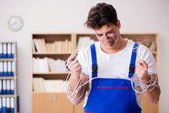 The funny young electrician tangled in cables. Funny young electrician tangled in cables Royalty Free Stock Photography
