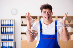 The funny young electrician tangled in cables. Funny young electrician tangled in cables Stock Photos
