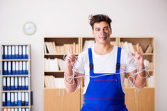 The funny young electrician tangled in cables Royalty Free Stock Images