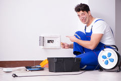 The funny young electrician working on socket at home Stock Photography
