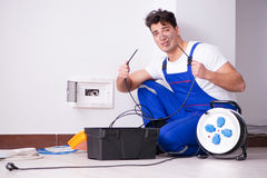 The funny young electrician working on socket at home. Funny young electrician working on socket at home Royalty Free Stock Images