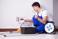 The funny young electrician working on socket at home. Funny young electrician working on socket at home Stock Photography