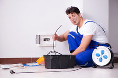The funny young electrician working on socket at home. Funny young electrician working on socket at home Royalty Free Stock Photo