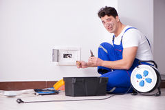 The funny young electrician working on socket at home. Funny young electrician working on socket at home Royalty Free Stock Image