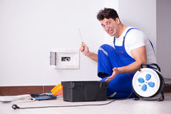 The funny young electrician working on socket at home Stock Photo