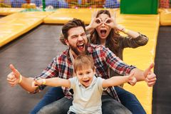 Funny young family with their little son spending time. On a trampoline together at the entertainment centre Royalty Free Stock Photos