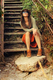 Funny young fashion girl sitting on the old wooden stairs. Stock Photo