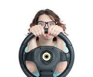 Funny young girl in glasses driver car with a steering wheel, isolated on white background stock images
