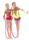 Funny young girl gymnasts show exercise. Royalty Free Stock Images