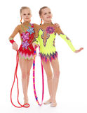 Funny young girl gymnasts show exercise. Stock Photo