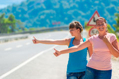 Funny young girl hitchhiking in mountains Royalty Free Stock Photography