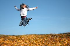 Funny young girl jumping outdoors Stock Photos