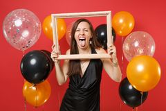 Funny young girl in little black dress celebrating showing tongue holding picture frame on bright red background air. Balloons. St. Valentine`s Day Happy New royalty free stock images