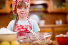 Funny young girl making mess in kitchen Stock Image