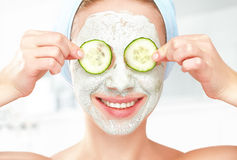 Funny young girl with a mask for skin face and cucumbers. On eyes Royalty Free Stock Photography
