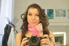 Funny young girl with a pink scarf and camera in her hands Stock Image