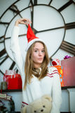 Funny young girl pulling christmas cap Royalty Free Stock Photos