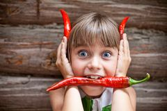 Girl with a red hot chili pepper in her mouth show devil horns. Funny young girl with a red hot chili pepper in her mouth showing red devil horns Royalty Free Stock Images