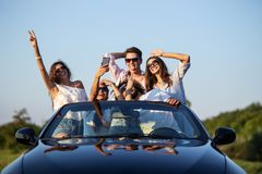 Funny young girls and guys in sunglasses are sitting in a black cabriolet on the road holding their hands up and making royalty free stock photography