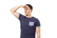 Adult men with emotions and gestures. Funny young guy squeezing his nose by hand due bad smell in the air isolated on white stock photography