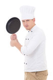 Funny young handsome man chef in uniform with teflon frying pan Royalty Free Stock Photography