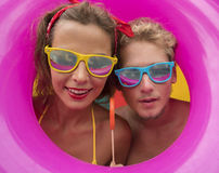 Funny young happy beach couple smiling  in the middle of pink inflatable ring. Funny young happy beach couple smiling  in the middle of pink inflatable ring Stock Images