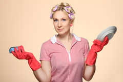 Funny young housewife with gloves holding scrubberr Stock Photos