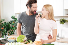 Funny young loving couple standing at kitchen and cooking Royalty Free Stock Photography