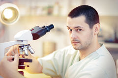 Funny Young Male Scientist with Microscope. Portrait of a male doctor looking through a microscope in a laboratory Stock Image
