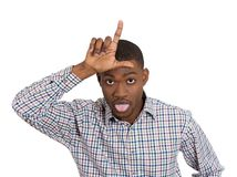 Funny young man displaying loser sign Stock Images