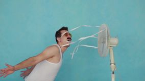 Funny young man with electric fan enjoying cool wind on blue background slow mo stock video