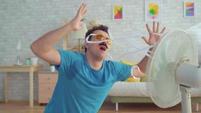 Funny young man with electric fan enjoying cool wind in his apartment stock footage