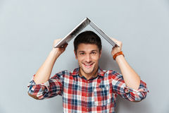 Funny young man having fun and making roof with laptop Royalty Free Stock Photography