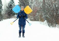 Funny young man holds two snow shovels, forming a symbol of Jolly Roger. Winter seasonal concept stock photography