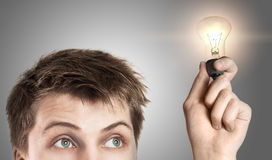 Funny young man with light bulb Stock Images