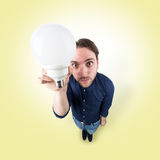 Funny young man with light bulb in his hand Royalty Free Stock Photo