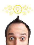 Funny young man with light  bulb over his head Royalty Free Stock Images