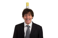 Funny young man with light  bulb over his head, isolated on white background Royalty Free Stock Photography
