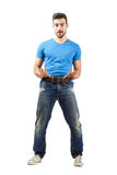 Funny young man pulling his belt Stock Image