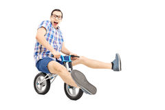 Funny young man riding a small bicycle Stock Photos