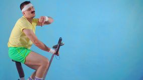 Young man from 80`s with mustache on exercise bike on blue background showing thumb down. Funny young man from 80`s with mustache on exercise bike on blue stock video
