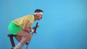 Funny young man from the 80`s with a mustache and glasses on exercise bike on a blue background slow mo stock footage