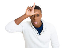 Funny young man showing loser sign on his forehead Royalty Free Stock Photography