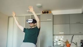 Funny young man in virtual reality 360 headset dancing in kitchen in the morning while listening to music and have fun Royalty Free Stock Photos