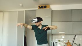 Funny young man in virtual reality 360 headset dancing in kitchen in the morning while listening to music and have fun Stock Image