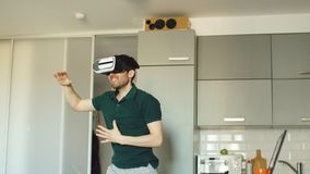 Funny young man in virtual reality 360 headset dancing in kitchen in the morning while listening to music and have fun Stock Images