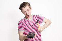 Funny, young man wants to destroy his hard disk. By hitting it with a hammer Stock Photo