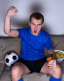 Funny young man watching football on tv and celebrating goal. Funny young man watching football on tv with chips and beer and celebrating goal Stock Image