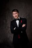 Funny young man wearing tuxedo on grey background Royalty Free Stock Image
