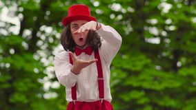 Funny young mime walks on stilts and juggling in the park. Comical young mime in wide red pants with suspenders, hat and a white shirt is juggling in the park stock footage